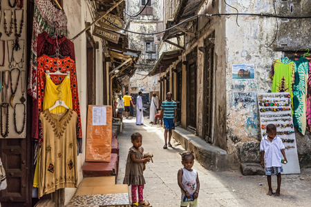 buildings town home: STONE TOWN, ZANZIBAR - OCTOBER 24, 2014: Local people on a typical narrow street in Stone Town. Stone Town is the old part of Zanzibar City, the capital of Zanzibar, Tanzania.