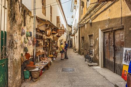 STONE TOWN, ZANZIBAR - OCTOBER 24, 2014: Tourists on a typical narrow street in Stone Town. Stone Town is the old part of Zanzibar City, the capital of Zanzibar, Tanzania.