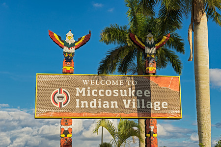 federally: MIAMI, FLORIDA - JANUARY 13, 2015 : Entrance sign in the Miccosukee Indian Village. The Miccosukee Tribe is a federally recognized Indian Tribe residing in the Florida Everglades west of Miami.