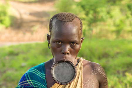 OMO VALLEY, ETHIOPIA - MAY 3, 2015 : Woman from the African tribe Surma with big lip plate. 에디토리얼