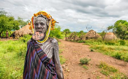 identidad cultural: Valle del Omo, Etiopía - 07 de mayo 2015: La mujer de la tribu africana Mursi con plato grande de labios en su pueblo.