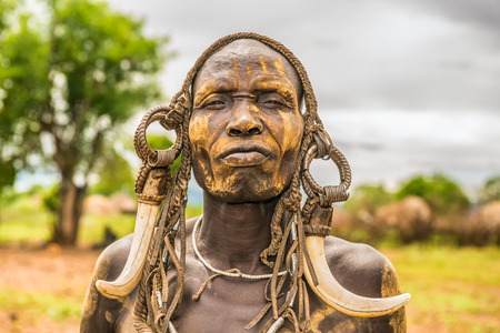 OMO VALLEY, ETHIOPIA - MAY 7, 2015 : Warrior from the african tribe Mursi with traditional horns in Mago National Park, Ethiopia.