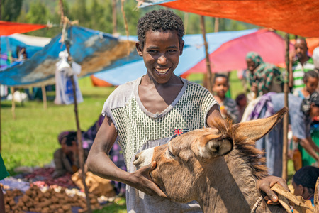 ethiopian ethnicity: JIMMA ETHIOPIA  MAY 2 2015 : Young ethiopian boy with his donkey at a popular local market  in Jimma. Editorial