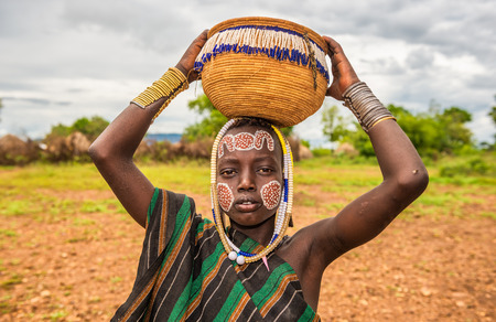 OMO VALLEY, ETHIOPIA - MAY 7, 2015 : Young boy from the African tribe Mursi with traditional jewelry in Mago National Park, Ethiopia.