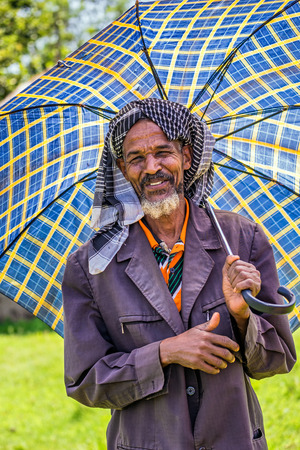 underdeveloped: JIMMA, ETHIOPIA - MAY 2, 2015 : Old ethiopian man with an umbrella on a hot day.