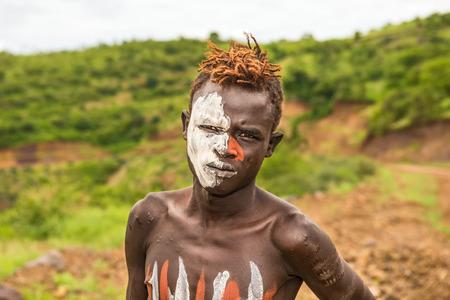 identidad cultural: Valle del Omo, Etiopía - 07 de mayo 2015: El muchacho joven de la tribu africana Mursi con la cara pintada tradicionalmente en el Parque Nacional de Mago, Etiopía. Editorial