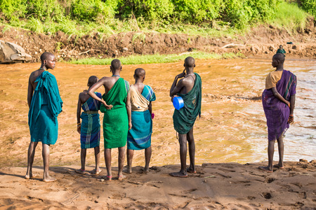 african tribe: OMO VALLEY, ETHIOPIA - MAY 3, 2015 : Young adults of the African tribe Suri standing on the banks of a river