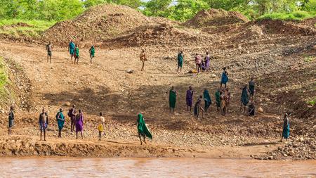 identidad cultural: Valle del Omo, ETIOP�A - 03 de mayo 2015: Los miembros de la tribu africana Suri pie en las orillas de un r�o Editorial