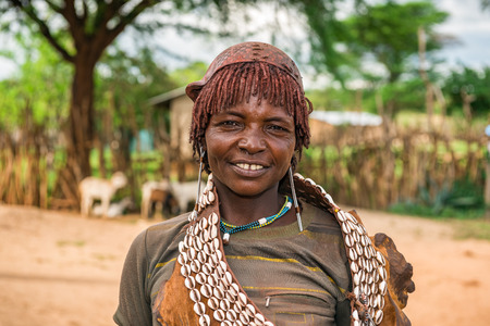 aboriginal woman: TURMI, OMO VALLEY, ETHIOPIA - MAY 5, 2015: Portrait of a woman from the Hamar tribe in south Ethiopia. Married hamar women apply red clay to their hair and fashion it into long tufts.
