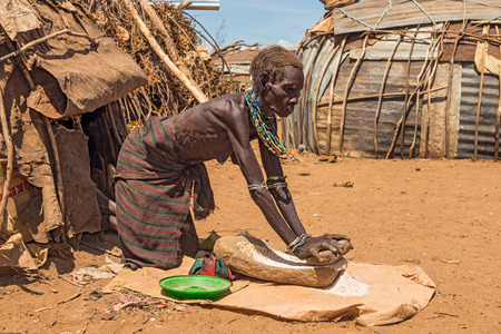 african tribe: OMO VALLEY, ETHIOPIA - MAY 6, 2015 : Old woman from the African tribe Dasanesh working hard in front of her hut. Editorial