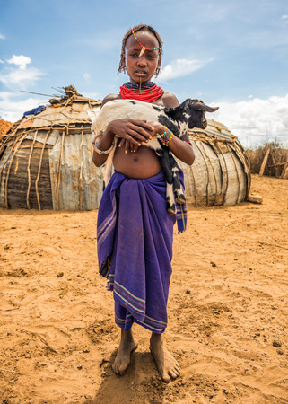 OMO VALLEY, ETHIOPIA - MAY 6, 2015 : Girl from the African tribe Dasanesh holding a goat in her village. 에디토리얼