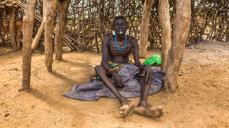 african tribe: OMO VALLEY, ETHIOPIA - MAY 6, 2015 : Old warrior from the african tribe Daasanach relaxing in his village.