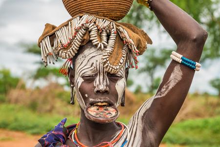 identidad cultural: Valle del Omo, Etiop�a - 07 de mayo 2015: La mujer de la tribu africana Mursi con plato grande de labios en su pueblo.