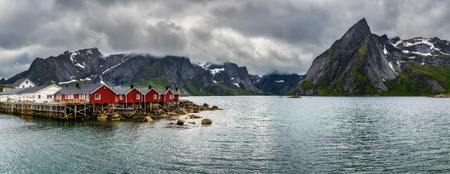 fishing cabin: Panorama of  mount Olstind above the red fishing cabins called Rorbu  in town of Hamnoy on Lofoten islands, Norway Stock Photo