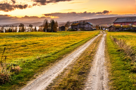 Iconic wooden barn with farmhouse and rural path at sunset in Norway