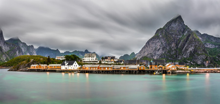 turquise: Panorama of  mount Olstind above the yellow cabins and turquise waters of Sakrisoy fishing village on Lofoten islands in Norway. Long exposure shot.