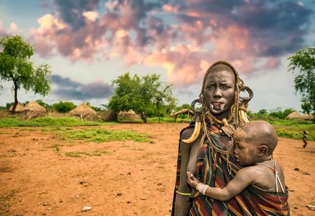 identidad cultural: Valle del Omo, ETIOP�A - 07 de mayo 2015: La mujer de la tribu Mursi africano con su beb� y los cuernos tradicionales en el parque nacional de Mago, Etiop�a Editorial