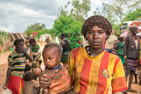 aboriginal woman: TURMI, OMO VALLEY, ETHIOPIA - MAY 5, 2015: Portrait of a woman from the Hamar tribe with her baby in south Ethiopia. Married hamar women apply red clay to their hair and fashion it into long tufts.