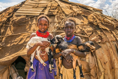 OMO VALLEY, ETHIOPIA - MAY 6, 2015 : Two girls from the African tribe Daasanach holding goats in front of their home. 에디토리얼