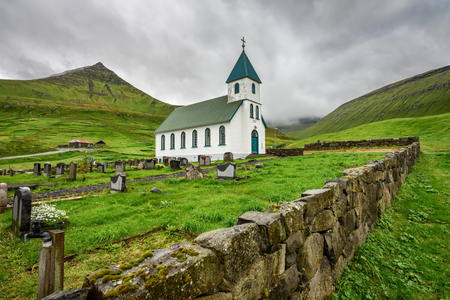 island: Small village church with cemetery in Gjogv located on the northeast tip of the island of Eysturoy, Faroe Islands, Denmark Stock Photo