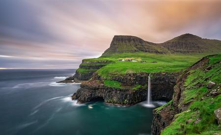 Landschap: Gasadalur dorp en zijn iconische waterval, Vagar, Faeröer, Denemarken. Lange blootstelling.