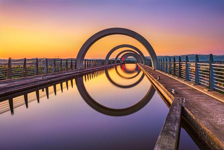 Falkirk Wheel al tramonto. Falkirk Wheel è un ascensore per le barche a rotazione in Scozia e collega il Forth e Clyde Canal con l'Union Canal. L'esposizione a lungo.