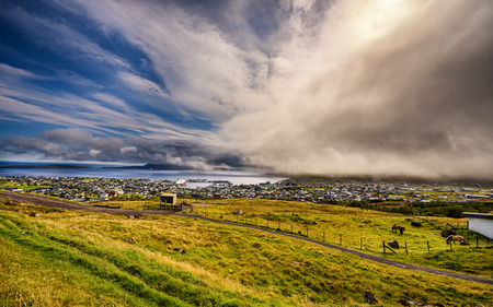 Dramatic change of weather over Torshavn, the capital and largest city of the Faroe Islands, Denmark. Hdr processed. Stock Photo