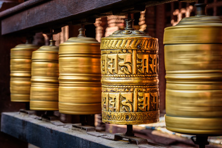 Golden tibetan prayer wheels in a Buddhist temple in Nepal