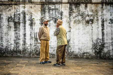 sidewalk talk: KATHMANDU, NEPAL - OCTOBER 21, 2015 : Two aged men discuss in the street at Pashupatinath Temple complex