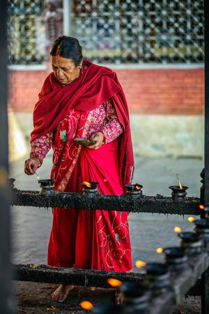 prayer candles: KATHMANDU, NEPAL - OCTOBER 20, 2015 : Elderly woman  lighting candles before prayer in a temple in Kathmandu