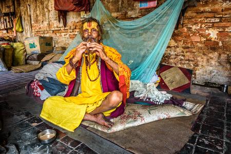 zampona: KATMANDU, NEPAL - 21 DE OCTUBRE, 2015: Sadhu baba (hombre santo) que viven en el templo de Pashupatinath juega un tubo Editorial