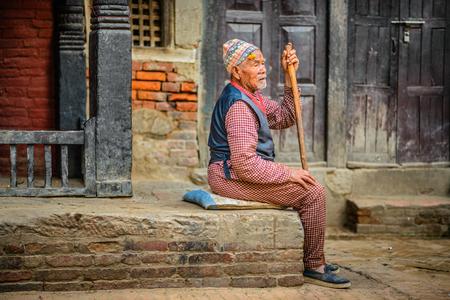 parapet: KATHMANDU, NEPAL - OCTOBER 21, 2015 : Elderly beggar with a walking stick sits in the street of Kathmandu