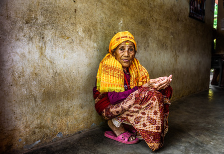 begs: KATHMANDU, NEPAL - OCTOBER 23, 2015 : Very old woman begs in a local retirement home Editorial