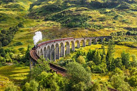 locomotora: Glenfinnan Viaducto de ferrocarril en Escocia con el tren de vapor jacobita pasando por encima Foto de archivo