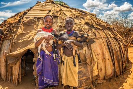 african tribe: OMO VALLEY, ETHIOPIA - MAY 6, 2015 : Two girls from the African tribe Daasanach holding goats in front of their home. Editorial