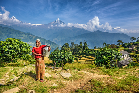 a jar stand: DHAMPUS, NEPAL - OCTOBER 27, 2015 : Nepalese woman in front of her home in the Himalayas mountains near Pokhara