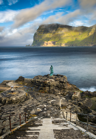 merman: Statue of Selkie or Seal Wife in the village of Mikladalur on Kalsoy, Faroe islands. Selkies are mythological creatures found in Irish, Scottish, and Faroese folklore. Long exposure.