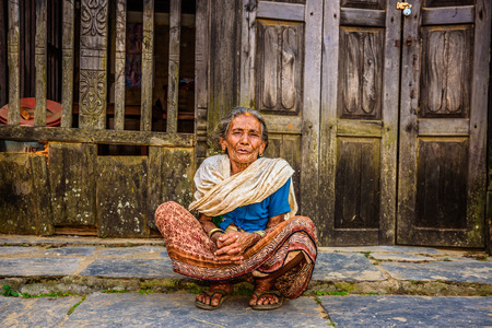 begs: BANDIPUR, NEPAL - OCTOBER 22, 2015 :  Old woman begs in the street of Bandipur