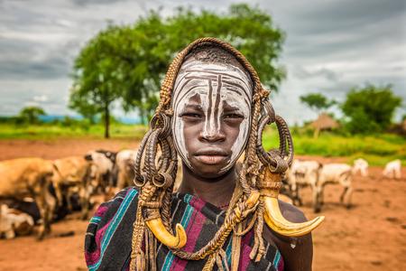 identidad cultural: Valle del Omo, ETIOP�A - 07 de mayo 2015: El muchacho joven de la tribu africana Mursi con cuernos tradicionales en el parque nacional de Mago, Etiop�a.