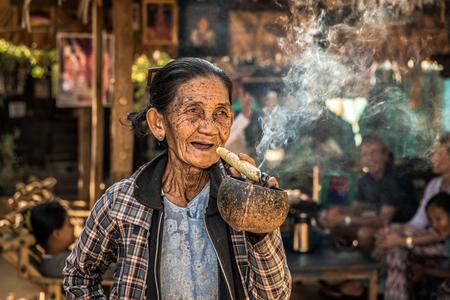 cheroot: BAGAN, MYANMAR - JANUARY 24, 2016 : Happy and old wrinkled woman smokes  a big cheroot cigar in public