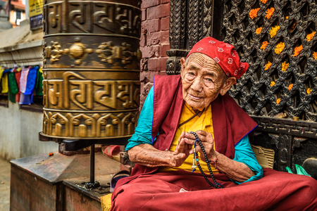begs: KATHMANDU, NEPAL - OCTOBER 28, 2015 : Very old tibetan buddhist nun sits and begs outside a shrine in Kathmandu