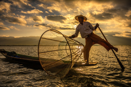 january sunrise: INLE LAKE, MYANMAR - JANUARY 28, 2016 : Burmese fisherman on a traditional bamboo boat catching fish  using a handmade net at sunrise