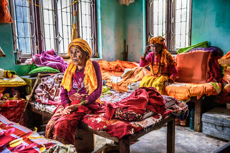gloominess: KATHMANDU, NEPAL - OCTOBER 23, 2015 : Elderly women sit on their beds in a retirement home Editorial