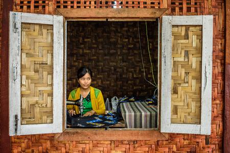 YANGON, MYANMAR - 21. JANUAR 2016: Junge asiatische Frau arbeitet an einer alten Nähmaschine Standard-Bild - 55917344