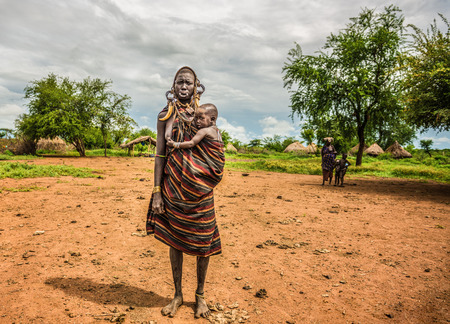 ethiopian ethnicity: OMO VALLEY, ETHIOPIA - MAY 7, 2015 : Woman from the african tribe Mursi with  her baby