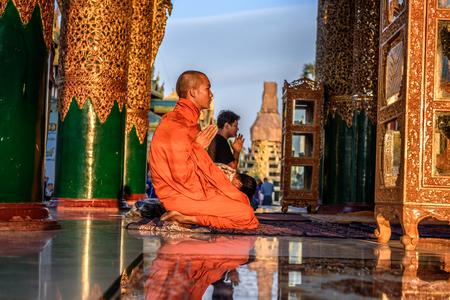 YANGON, MYANMAR - JANUARY 18, 2016 : Asian monk prays  in the Shwedagon Pagoda Temple at sunset.
