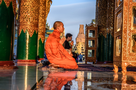YANGON, MYANMAR - JANUARY 18, 2016 : Asian monk prays  in the Shwedagon Pagoda Temple at sunset.