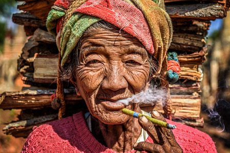 cheroot: IN DEIN, MYANMAR - JANUARY 27, 2016 : old wrinkled woman smokes  a cheroot cigar Editorial