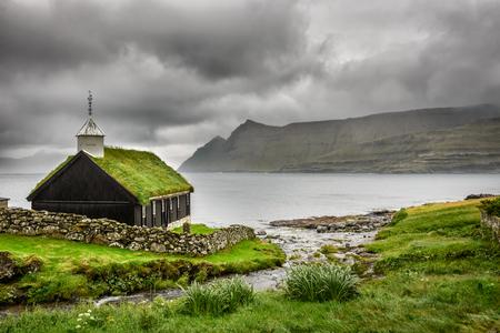 重い雲の下で Funningur の小さな村の教会。Funningur は、Eysturoy 島、フェロー諸島、デンマークにあります。