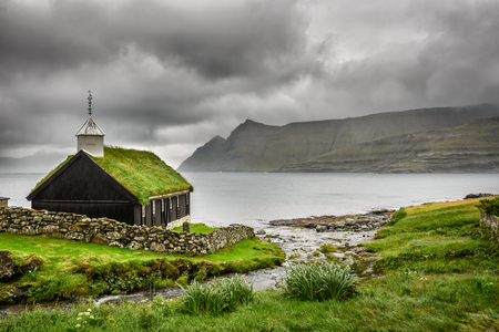 Small village church in Funningur under heavy clouds. Funningur is located on the island of Eysturoy, Faroe Islands, Denmark